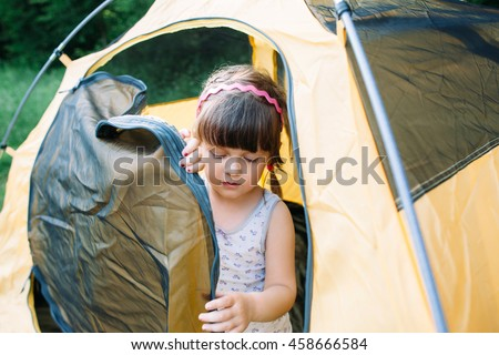 Little girl getting out of tent in forest. Young girl-scout studying camping lifestyle.