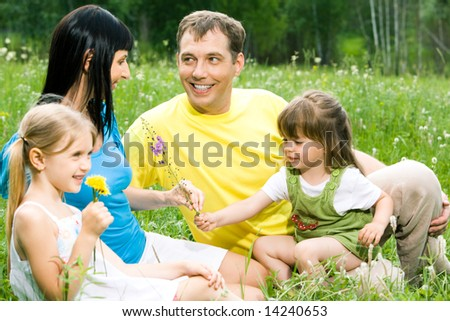 Little girl giving flower to her mother with father and sister near by