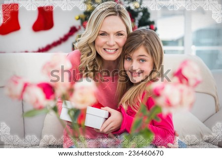 Little girl giving her mother a christmas gift against snowflake frame - stock photo