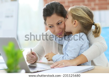 Little girl giving kiss to her mom while working from home - stock photo