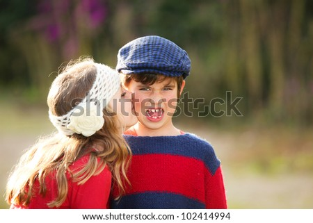 little girl giving kiss to young embarrassed boy. - stock photo