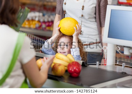 Little girl giving muskmelon to female cashier at counter for billing in supermarket - stock photo