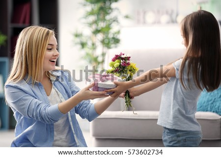 Little girl giving present to her mother at home. Mother's day concept
