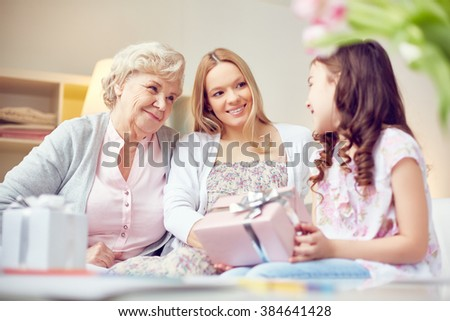 Little girl giving presents to her mother and grandmother - stock photo