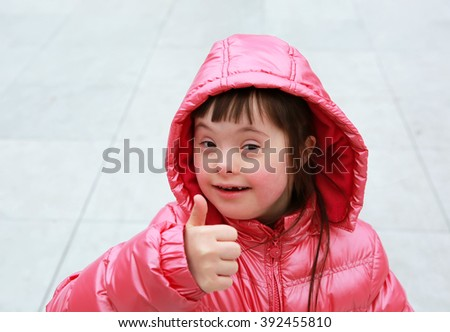 Little girl giving thumbs up on the grey background - stock photo