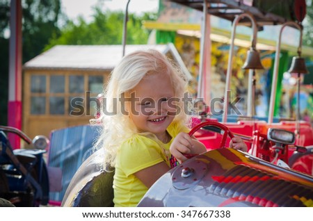 Little girl goes for a drive on a children's attraction