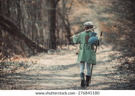 little girl goes on a footpath in the forest with stuff, photo in retro style - stock photo