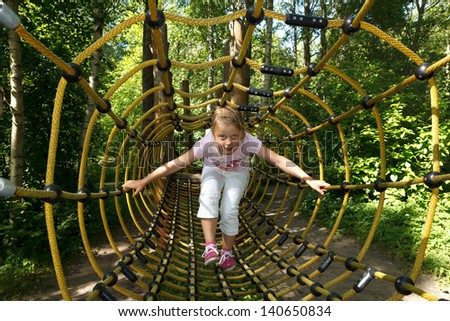 little girl going trough tunnel in forest attraction park - stock photo