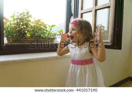 little girl hamming near window - stock photo