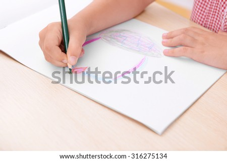 Little girl hands and her drawing at the desk in classroom
