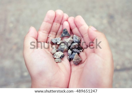 little girl hands holding small stones