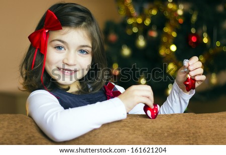 Little girl  hanging toy on Christmas tree - stock photo