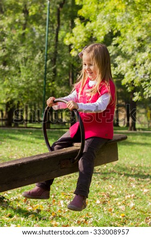 Little girl have fun in the park. Autumn season.
