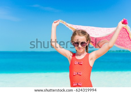 Little girl have fun with beach pareo on tropical vacation