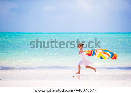 Little girl have fun with beach towel during tropical vacation