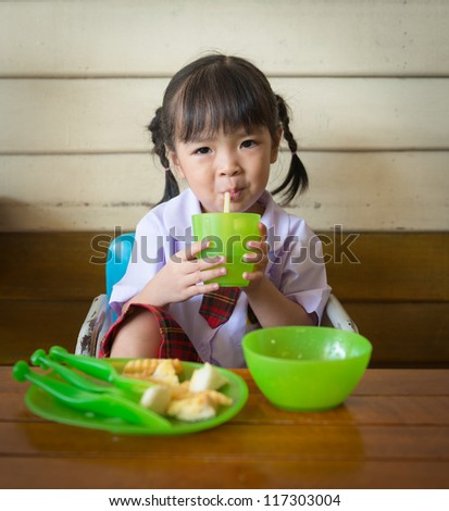 little girl have lunch at restaurant - stock photo