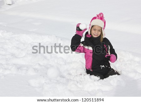 Little girl having a snowball fight - stock photo