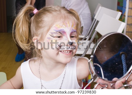 Little girl having face painted on birthday party - stock photo