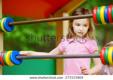 Little girl having fun at a playground on summer day - stock photo