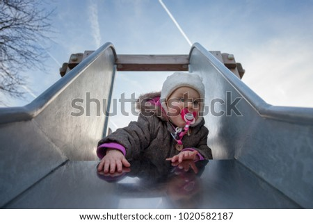 little girl having fun at the playgound and sliding down the childrens slider