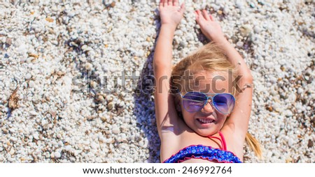 Little girl having fun enjoying vacation on tropical beach with white sand and turquoise ocean water - stock photo