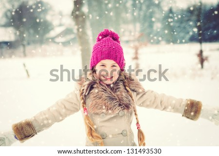 little girl having fun in snow - stock photo