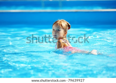 Little girl having fun in swimming pool - stock photo