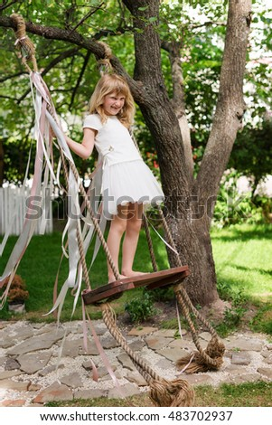 Little girl having fun on a swing outdoor. Child playing, garden playground