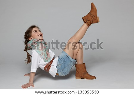Little girl having fun on the studio floor - stock photo