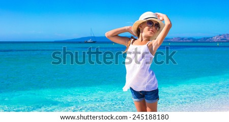 Little girl having fun on tropical beach with white sand and turquoise ocean water - stock photo