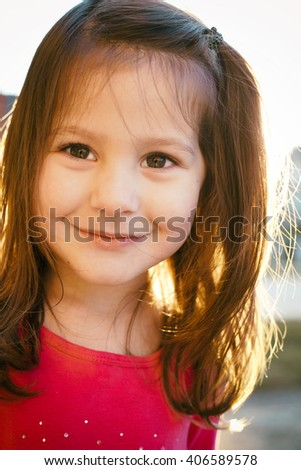 little girl having fun outdoors wearing pink shirt during sunset - stock photo