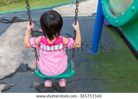 Little girl having fun  playing swing at the park
