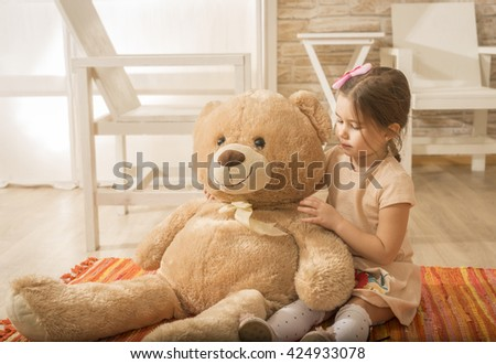 Little girl having fun with plush bear toy. Playing with teddy bear at home. Childhood happiness concept. Portrait of expressive charming little girl hugging huge plush bear - stock photo