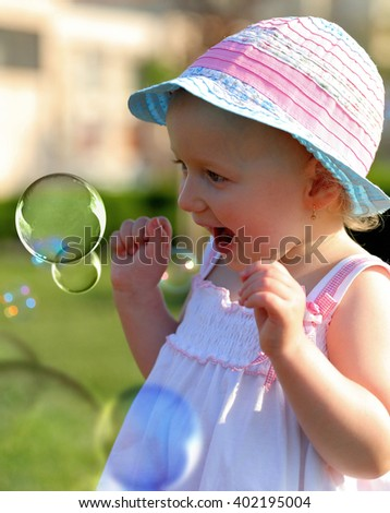 Little girl having fun with some soap bubbles - stock photo