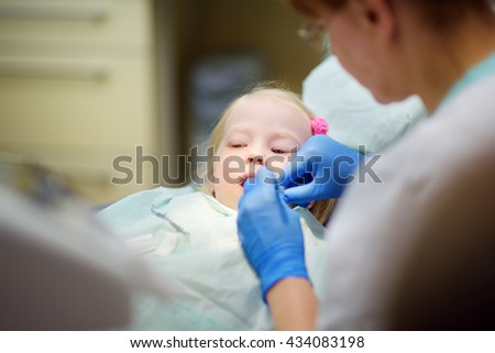 Little girl having her teeth examined by dentist in dental clinic - stock photo