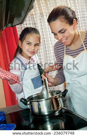 Little girl help her mother in kitchen - stock photo