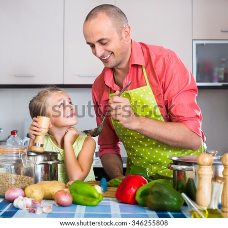 Little girl helping american father to prepare dinner indoors - stock photo