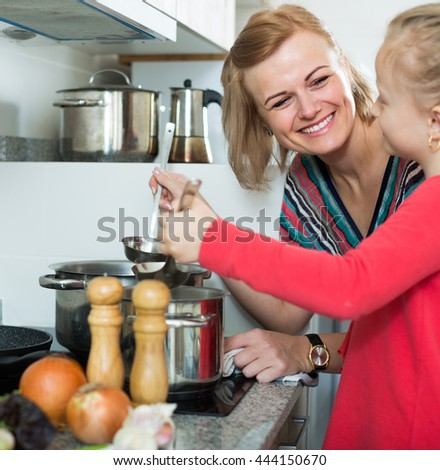 Little girl helping cheerful smiling mother to prepare meal at kitchen - stock photo