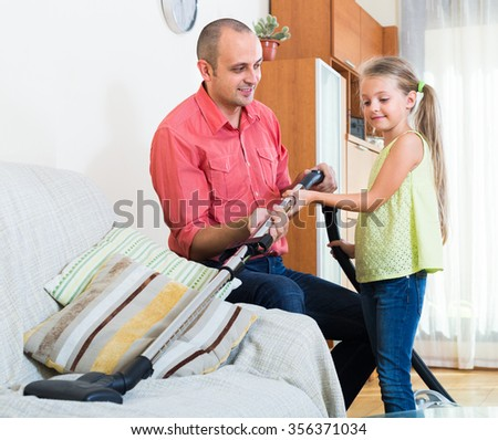 Little girl helping father to do regular clean-up in flat