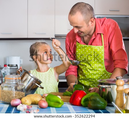 Little girl helping father to prepare dinner in interior - stock photo