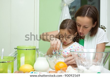 little girl helping her mother to bake a cake