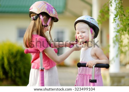 Little girl helping her sister to put a bicycle helmet on - stock photo