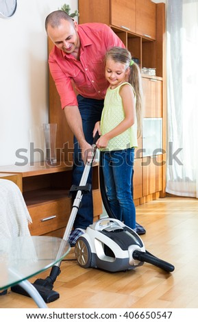 Little girl helping man to do regular clean-up indoors