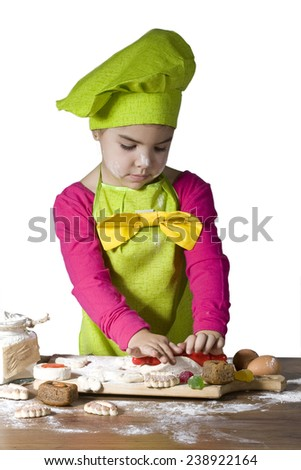 Little girl helps cook bake cookies for the holiday - stock photo