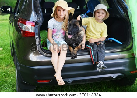 little girl , her brother and dog sits in car