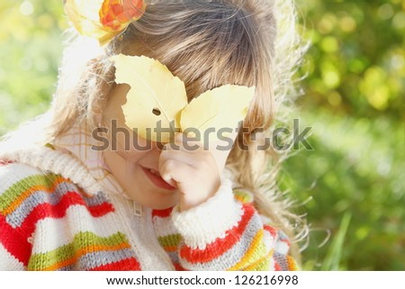 Little Girl Hiding Behind the Leaf on Sunny Autumn Day - stock photo