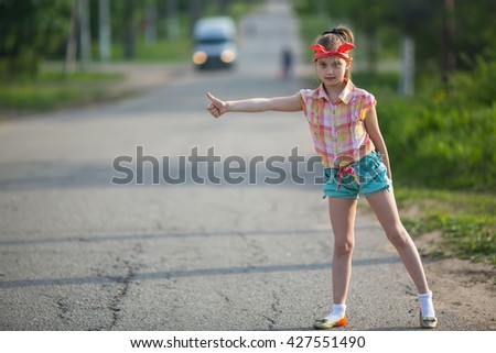 Little girl hitchhiking along a road. - stock photo