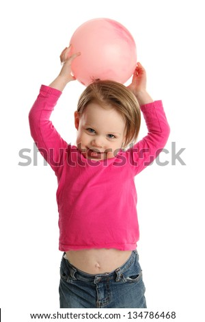Little girl holding a ball over her head getting ready to throw it, showing her belly button under her shirt - stock photo
