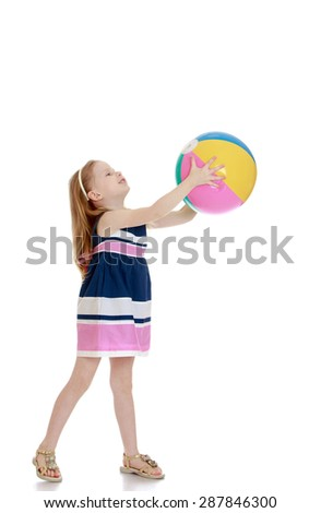 Little girl holding a beach ball in his outstretched hands-isolated on white background - stock photo