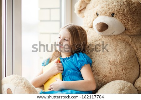 Little girl holding a book on windowsill with big toy